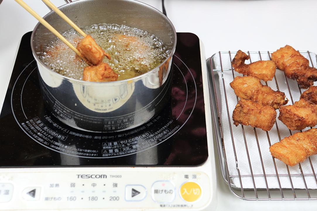 油で下味を付けた豚肉を揚げる
