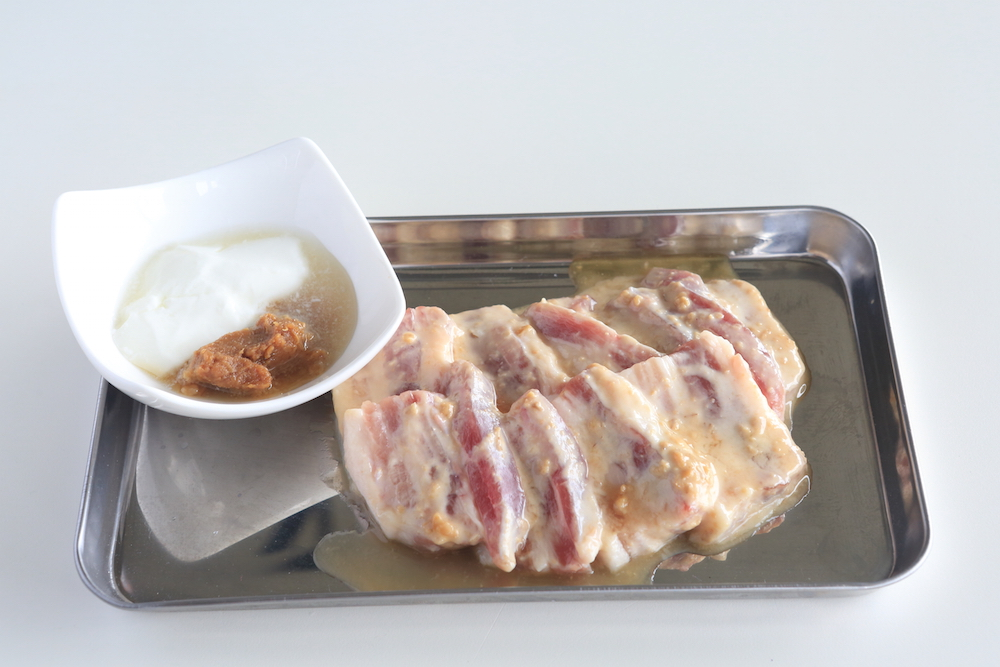 豚バラブロックをカットし、輝麦とヨーグルト・はちみつに漬け込みます。